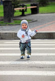 Rapaz pequeno que cruza uma rua Imagem de Stock Royalty Free