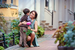 Rapaz pequeno que dá a flor a sua mamã fotos de stock