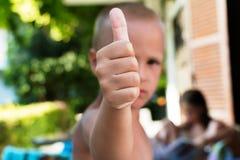 Rapaz pequeno que dá os polegares acima imagem de stock royalty free