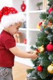 Rapaz pequeno que decora a árvore de Natal Fotos de Stock