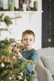Rapaz pequeno que decora a ?rvore de Natal com brinquedos e bolas Crian?a bonito que prepara-se em casa para a celebra??o do xmas fotos de stock royalty free