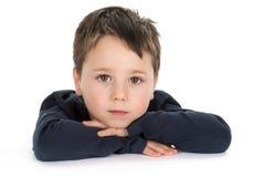 Rapaz pequeno que descansa em suas mãos Imagem de Stock Royalty Free
