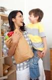 Rapaz pequeno que desembala o saco de mantimento com sua matriz Imagem de Stock Royalty Free
