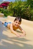 Rapaz pequeno que desliza para baixo a corrediça de água imagem de stock