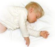 Rapaz pequeno que dorme nos bedclothes brancos fotografia de stock