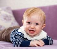 Rapaz pequeno que encontra-se no sofá imagem de stock royalty free