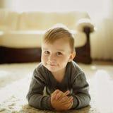 Rapaz pequeno que encontra-se no tapete imagens de stock