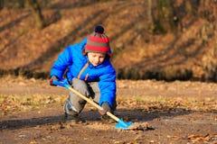 Rapaz pequeno que escava no parque do outono Fotografia de Stock Royalty Free