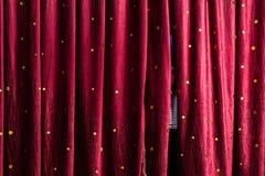 Rapaz pequeno que espreita atrás das cortinas da fase Fotografia de Stock