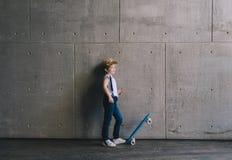 Rapaz pequeno que está com um skate Imagem de Stock Royalty Free