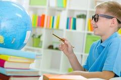Rapaz pequeno que estuda sobre o mundo Imagem de Stock Royalty Free