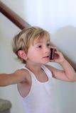 Rapaz pequeno que fala no telefone de pilha Foto de Stock Royalty Free
