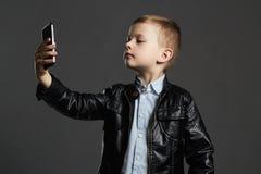 Rapaz pequeno que faz o selfie criança à moda no revestimento e no chapéu de couro Caçoa a emoção Fotografia de Stock