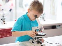 Rapaz pequeno que faz a pesquisa da bioquímica no laboratório Um menino da aparência europeia em um polo conduz experiências biol imagens de stock