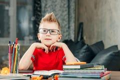 Rapaz pequeno que faz trabalhos de casa na escola foto de stock