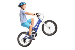 Rapaz pequeno que faz um wheelie em uma bicicleta azul pequena Fotos de Stock