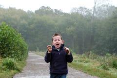 Rapaz pequeno que grita para fora nas madeiras foto de stock
