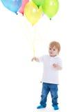 Rapaz pequeno que guarda balões em um fundo branco Foto de Stock