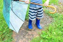 Rapaz pequeno que guarda o guarda-chuva verde imagens de stock royalty free