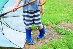 Rapaz pequeno que guarda o guarda-chuva verde foto de stock