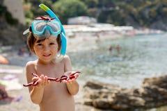 Rapaz pequeno que guarda o vermelho cinco estrelas do mar do ponto em suas mãos no Imagens de Stock Royalty Free