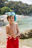 Rapaz pequeno que guarda o vermelho cinco estrelas do mar do ponto em suas mãos no Imagem de Stock
