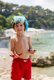 Rapaz pequeno que guarda o vermelho cinco estrelas do mar do ponto em suas mãos no Fotos de Stock