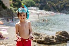 Rapaz pequeno que guarda o vermelho cinco estrelas do mar do ponto em suas mãos no Imagens de Stock