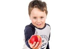 Rapaz pequeno que guarda a partilha de uma maçã Coma isto Imagens de Stock Royalty Free