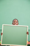Rapaz pequeno que guarda um balckboard Fotografia de Stock