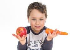 Rapaz pequeno que guarda uma maçã e uma cenoura Foto de Stock
