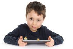 Rapaz pequeno que guarda uma tabuleta Imagens de Stock