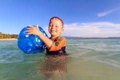 Rapaz pequeno que joga a bola na água Imagem de Stock
