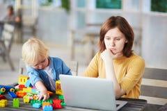 Rapaz pequeno que joga com blocos da construção quando sua mãe que trabalha no computador imagem de stock royalty free