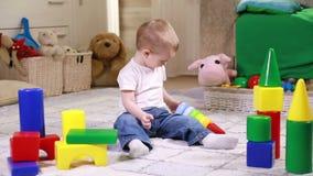 Rapaz pequeno que joga com blocos da cor video estoque