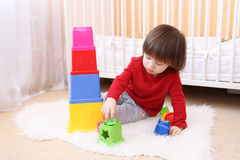 Rapaz pequeno que joga com brinquedo educacional em casa Foto de Stock Royalty Free