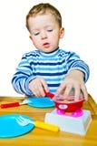Rapaz pequeno que joga com cozinha do brinquedo foto de stock royalty free