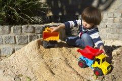 Rapaz pequeno que joga com escavador do brinquedo e caminhão de descarregador Imagem de Stock