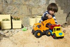 Rapaz pequeno que joga com escavador do brinquedo e caminhão de descarregador Fotos de Stock Royalty Free