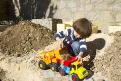 Rapaz pequeno que joga com escavador do brinquedo e caminhão de descarregador Foto de Stock