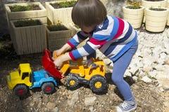 Rapaz pequeno que joga com escavador do brinquedo e caminhão de descarregador Fotografia de Stock