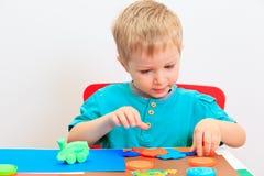 Rapaz pequeno que joga com massa da argila fotografia de stock