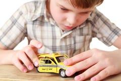Rapaz pequeno que joga com o táxi do amarelo do brinquedo Imagem de Stock Royalty Free