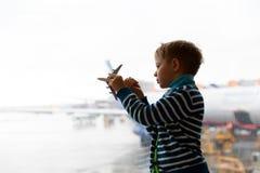 Rapaz pequeno que joga com plano do brinquedo no aeroporto Imagem de Stock