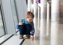 Rapaz pequeno que joga com plano do brinquedo no aeroporto Fotografia de Stock Royalty Free