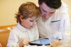 Rapaz pequeno que joga com seu irmão mais idoso com PC da tabuleta Fotografia de Stock Royalty Free