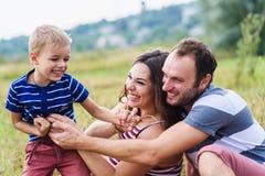 Rapaz pequeno que joga com seus pais Foto de Stock