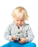 Rapaz pequeno que joga com telefone esperto Foto de Stock Royalty Free