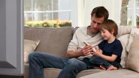 Rapaz pequeno que joga com um controlo a distância vídeos de arquivo