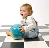 Rapaz pequeno que joga com um globo Fotos de Stock